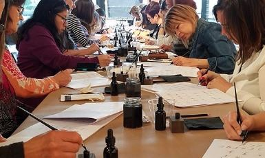 Group of people at a calligraphy class practicing lettering